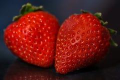 Rode aardbeien op zwarte glanzende achtergrond met bezinning Stock Foto's