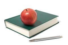 Rode appel en groen boek stock foto