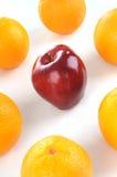 Rode appel in het midden van sinaasappel Stock Afbeelding