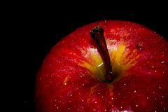 Rode appel met druppeltjes van water tegen zwarte achtergrond met ruimte voor tekst stock afbeelding