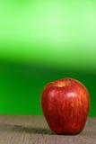 Rode appel met groene achtergrond Stock Fotografie