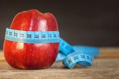 Rode appel met het meten van band om lengte op een houten achtergrond te meten, dieet, gezonde levensstijl Stock Foto