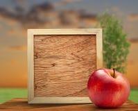 Rode appel met houten kader stock fotografie