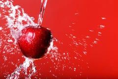 Rode appel onder het bespatten op een rode achtergrond Stock Foto's