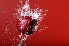 Rode appel onder het bespatten op een rode achtergrond Royalty-vrije Stock Foto