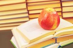 Rode appel op de open boeken stock foto's