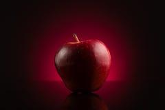 Rode appel op donkerrode achtergrond Royalty-vrije Stock Foto