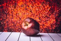 Rode appel op een witte houten lijst Defocusedachtergrond bukeh Stock Foto's