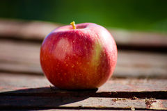 Rode appel op houten lijst stock foto's