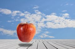 Rode appel in surreal landschap met bewolkte hemel Stock Afbeelding