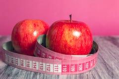 Rode appel twee met het meten van band op roze achtergrond Gezond dieetconcept Stock Foto's