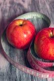 Rode appel twee met het meten van band op roze achtergrond Gezond dieetconcept Stock Foto