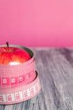 Rode appel twee met het meten van band op roze achtergrond Gezond dieetconcept Royalty-vrije Stock Afbeelding