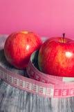 Rode appel twee met het meten van band op roze achtergrond Gezond dieetconcept Royalty-vrije Stock Afbeeldingen