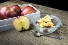 Rode appelen in de kom en Appelen in het vakje op de houten lijst Stock Afbeeldingen