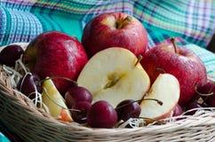 Rode appelen en kers op een handdoek Stock Afbeelding