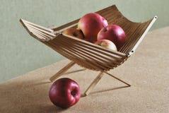 Rode appelen in houten mand op groene achtergrond Stock Fotografie