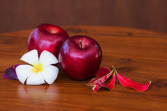 Rode appelen met bloem en bladeren op houten bruine lijst stock fotografie