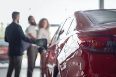 Rode auto dichte omhooggaand, cliënten van het autohandel drijven erachter royalty-vrije stock foto