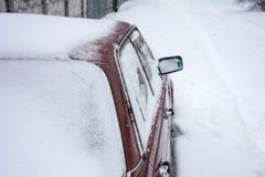 Rode auto die met sneeuw wordt behandeld royalty-vrije stock foto's