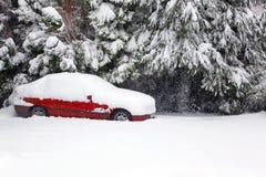 Rode auto die in sneeuw wordt behandeld Stock Foto's