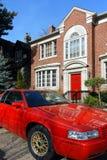 Rode auto die voor huis wordt geparkeerd Stock Fotografie