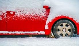 Rode auto onder sneeuw stock afbeelding