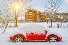 Rode auto onder sneeuw stock fotografie