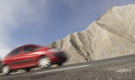 Rode auto in zich het bewegen in een dor landschap stock afbeelding