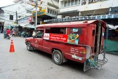Rode autotaxi die de straten wordt doorgenomen die klanten zoeken Stock Foto