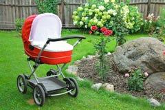 Rode babywandelwagen op aard in park Stock Afbeeldingen