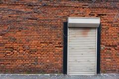 Rode bakstenen muur en ijzer gesloten deur Stock Afbeeldingen