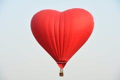 Rode ballon in de vorm van een hart tegen de blauwe hemel Stock Foto