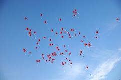 Rode ballons met bladen die in de blauwe hemel vliegen Stock Afbeelding