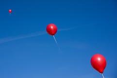 Rode ballons op blauwe hemel Stock Afbeeldingen