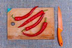 Rode bittere, hete peper die op houten scherpe raad liggen royalty-vrije stock foto's