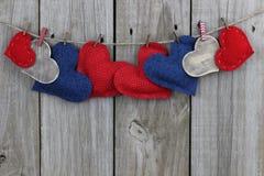 Rode, blauwe en houten harten die op drooglijn met houten achtergrond hangen Royalty-vrije Stock Foto's