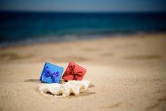 Rode, blauwe giftdozen op het zandige strand, achtergrondoverzees Royalty-vrije Stock Fotografie