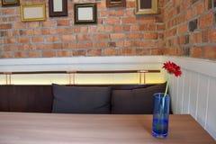 Rode Bloemen in een glas op de lijst Bakstenen muur en kaderachtergrond stock foto's