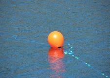 Rode boei met blauwe kabel in water die een anker merken Royalty-vrije Stock Foto's