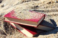 Rode boeken op het zand Stock Afbeelding