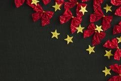 Rode bogen en gele sterren op zwarte achtergrond Stock Afbeelding