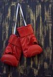Rode bokshandschoenen die op een spijker hangen royalty-vrije stock foto's