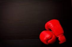 Rode bokshandschoenen op een zwarte achtergrond in de hoek van het kader Stock Afbeeldingen