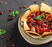 Rode boon met nachos of pitabroodjespaanders, peper en greens op plaat over donkere achtergrond Mexicaanse snack, Vegetarisch voe royalty-vrije stock foto's