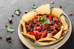 Rode boon met nachos of pitabroodjespaanders, peper en greens op plaat over donkere achtergrond Mexicaanse snack, Vegetarisch voe royalty-vrije stock fotografie