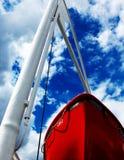 Rode boot en blauwe hemel stock foto