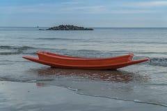 Rode boot op het strand Stock Fotografie