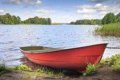 Rode boot op kust op achtergrond van schilderachtig landschap van meer en groene aard rond in heldere zonnige de zomerdag Royalty-vrije Stock Afbeeldingen