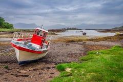 Rode boten op de kust at low tide, Schotland Stock Afbeeldingen